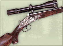 Break open single shot rifle with sidelock, custom engraving and custom carving on stock.
